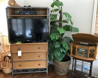Wicker media cabinet, flat screen TV, baskets, faux palm tree and  record/CD player