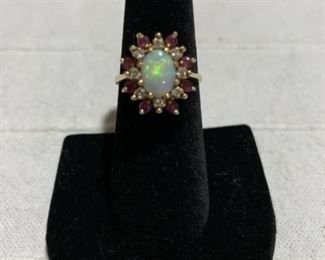 Opal ring with diamond's and ruby's, 14 karat yellow gold. Weighs 4.6 grams and is a size 6 1/2 to 7.
