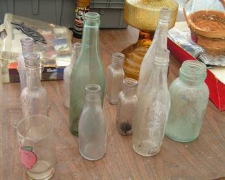 bottles with writing on them plus amber colored oil lamp
