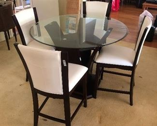Glass top kitchen table and white vinyl chairs