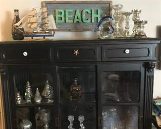 The black display case has been sold but all the decorative pieces are still available.  Model ship with awesome details!  Lots of mercury glass, metal beach sign lights up!!