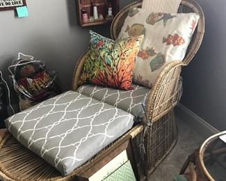 Nice wicker chair with foot rest.  Notice in background - a collection of vintage Lefton Lighthouses in a cool boat display case.  House is filled with beautiful decorative pillows as well.