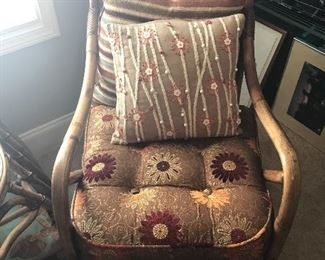 Nice wicker chair with beautiful textured pillows.