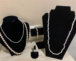 Selection of ladies pearl jewelry. Peach color pearl necklace says 14 K and small seed pearl necklace says 14 K. Necklace on right is stamped 925 and measures approximately 32 inches long. The bracelet and ring are costume, the ring is size 6 1/2.