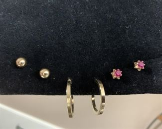 Three pair of gold earrings. Gold ball post studs are stamped 14 K on the earring back's. Red stones appear to be Ruby but cannot say for sure. Gold loops stamped Italy 14 K.