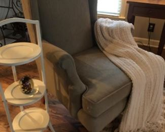 Gray scaled wing back chair, shown with pie shelf tables and afghan
