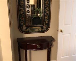 mahogany demilune table below painted mirror