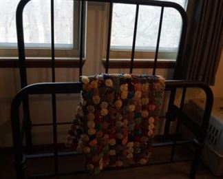 iron bed made into a quilt rack