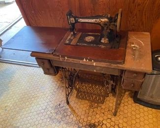 """Antique Sewing Machine Measures 48"""" long folded out, 34"""" folded in. 16"""" across x 29"""" to top of table."""