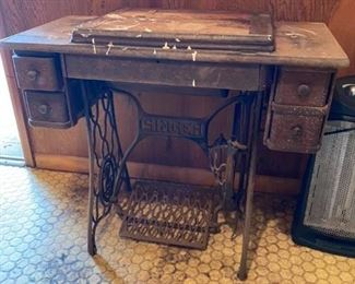 """Antique Sewing Machine Measures 48"""" long folded out, 34"""" folded in. 16"""" across x 29"""" to top of table"""