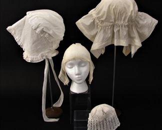 Antique bonnets, caps, one baby