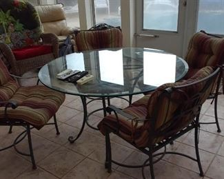 Glass top patio table and four chairs with cushions