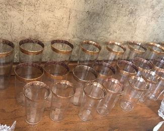 Full set of elegant glassware with etched gold trim along the rim.