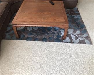 Living room coffee table and sable colored rug with blue accents
