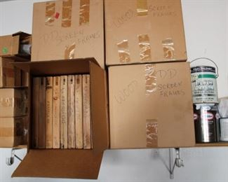 Boxes to the left full of silk screen material, the boxes in front are framed silk screen completed pieces.