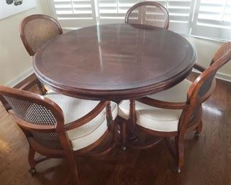 Beautiful dining room table and 4 chairs. Pedestal table has parquet design on top. The 4 chairs have a cane back, white fabric seat and they are on wheels.  https://ctbids.com/#!/description/share/756684
