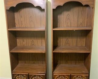 Two matching wooden bookcases with 2 fixed shelves and a storage cabinet below featuring beautiful and artistic scroll patterns in the wood embellishments on the doors with brass key style handles. 26x13x72 Shelves: 24x13x18 and 15 Cabinet: 25x13x17  https://ctbids.com/#!/description/share/755973