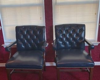 A set of two executive office chairs each in good condition and finished with brass studs for accents. There are some noticeable holes in the material but they are small and some minimal scuffing is present on the wood legs. 23x30x36  https://ctbids.com/#!/description/share/755993