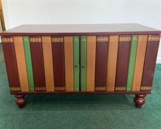 This is a book cabinet from The Bombay Company features two matching doors resembling a shelve of books. Single level area for storage. Minor scratches on surface areas and feet. 36x16x20 Inside: 34x15x14  https://ctbids.com/#!/description/share/755979