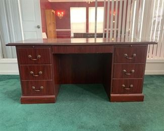 An Executive desk made of Mahogany wood with minor scratches along the edges and some corners. 5 pull out drawers and two pull out surfaces on each side of the desk. 66x31x30 Drawers Top: 13x20x3 Middle: 25x17x1.5 Bottom: 12x20x9  https://ctbids.com/#!/description/share/755985