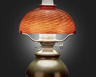 "2 A Tiffany Studios Favrile Glass Table Lamp Circa 1902-1919; New York, NY Shade signed: L.C.T. / Favrile The red and gold damascene Favrile glass shade on a single-light patinated bronze converted oil lamp base with glass hurricane chimney, electrified Overall: 19.5"" H x 10"" Dia. Estimate: $2,500 - $3,500"