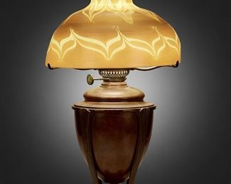 "4 A Tiffany Studios Favrile Glass Table Lamp Circa 1900-1902; New York, NY Shade signed: L.C.T.; Base signed: Tiffany Studios / New York / [T.G.D.Co. monogram] / D 548 The gold iridescent Favrile glass shade with pulled feather motif and tones of purple and brown on a single-light patinated bronze ""Greek"" converted oil lamp base with glass hurricane chimney, electrified Overall: 23"" H x 12"" Dia. Estimate: $3,000 - $5,000"