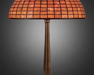 "5 A Tiffany Studios Geometric Table Lamp Circa 1902-1919; New York, NY Shade signed: Tiffany Studios / New York / 1436; Base unsigned The caramel-colored leaded glass geometric shade with square brick pattern on a three-light patinated bronze base, electrified Overall: 21.5"" H x 16"" Dia. Estimate: $2,500 - $3,500"