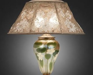 "1 A Tiffany Studios Favrile Glass Table Lamp Circa 1919-1928; New York, NY Shade signed: Louis C. Tiffany Furnaces, Inc. / [L.C.T. monogram] / Favrile / 903 / Pat. Appd. For; Base signed: Louis C. Tiffany Furnaces, Inc. / [L.C.T. monogram] Favrile / 81 A The enameled metal mesh shade with embossed Queen Anne's lace motif, green enameling to interior, white enameling to exterior, brass rope-style borders, and art glass finial on a two-light Favrile glass base with flower and stem motifs raised on a gilt-bronze foot with stylized foliate designs and inset enameled details, electrified Overall: 23"" H x 18"" Dia. Estimate: $3,000 - $5,000"