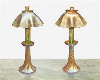 "8 A Near-Pair Of L.C. Tiffany Favrile Glass Candle Lamps Circa 1892-1919; New York, NY Each signed: L.C.T.; One base with partial L.C.T. monogram paper label Each gold iridescent Favrile glass with swirled base terminating in a bobeche issuing a glass candle holder with green pulled feather motif fitted with a metal knob to control the wick and topped with a scalloped onion skin shade, 2 pieces Each: 14.5"" H x 7.25"" Dia. Estimate: $3,000 - $5,000"