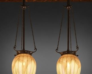 "7 A Pair Of L.C. Tiffany Favrile Glass Pendant Lights First-quarter 20th Century; New York, NY Shades signed: L.C.T. Each teardrop-shaped gold iridescent Favrile glass shade with green pulled feather motif fitted with an associated single-light patinated metal stem, canopy, and three beaded harnesses, electrified Each: 24"" H x 5.25"" Dia. Estimate: $2,000 - $3,000"