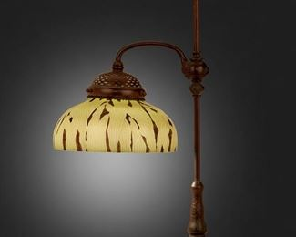 """13 A Tiffany Studios Adjustable Table Lamp 1902; New York, NY Shade signed: L.C.T. / 624; Base signed: [T.G.D.Co. monogram] / Tiffany Studios / New York / 25858 The green and black Favrile glass shade with leaf motif on a patinated bronze adjustable, single swing arm base with bead designs and engraved swirl and scale motifs, electrified Overall: 25.5"""" H x 14"""" Dia.; Shade: 10"""" Dia. Estimate: $3,000 - $5,000"""