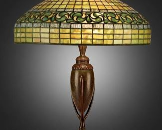 "12 A Tiffany Studios ""Vine Border"" Table Lamp Circa 1902-1919; New York, NY Shade signed: Tiffany Studios / New York / 1470; Base signed: Tiffany Studios / New York / 441 / [T.S. monogram] The green and blue leaded glass ""Vine Border"" shade on a three-light patinated bronze narrow urn-form ""Greek"" base, electrified Overall: 21.5"" H x 18"" Dia. Estimate: $8,000 - $12,000"