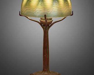 """14 A Tiffany Studios Bronze Boudoir Lamp With Art Glass Shade Circa 1902-1919; New York, NY Shade marked: S 9069; Base signed: Tiffany Studios / New York / S 934 / 324 The iridescent green and blue Tiffany-style glass shade on a single-light patinated bronze Tiffany Studios base with iridescent jewels and floral motif, electrified Overall: 14"""" H x 7"""" Dia. Estimate: $3,000 - $5,000"""