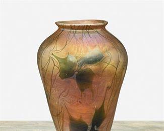 "21 A L.C. Tiffany Favrile Glass Leaf And Vine Vase 1908; New York, NY Signed: L.C. Tiffany / Favrile / 4405 C The urn-form marbled gold iridescent Favrile glass vase with green iridescent leaf and vine motif 7"" H x 5"" Dia. Estimate: $1,000 - $1,500"