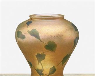 "22 A L.C. Tiffany Favrile Glass Leaf And Vine Vase 1912; New York, NY Signed: L.C. Tiffany / Favrile / 2795 G The wide-shouldered gold iridescent Favrile glass vase with green iridescent leaf and vine motif 6.5"" H x 6"" Dia. Estimate: $800 - $1,200"