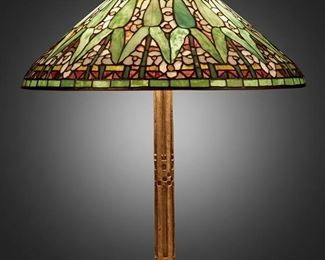 """23 A Tiffany Studios """"Arrowroot"""" Table Lamp First-quarter 20th Century; New York, NY Shade signed: Tiffany Studios / New York; Base signed: Tiffany Studios / New York / 528 The polychrome leaded glass """"Arrowroot"""" shade on a three-light gilt-bronze """"Fifteenth Century"""" base with straight column and incised square patterning, electrified Overall: 25"""" H x 20.75"""" Dia. Estimate: $30,000 - $40,000"""