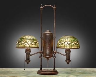 """26 A Tiffany Studios Double-Arm Student Lamp 1901; New York, NY One shade signed: Tiffany Studios / New York; Base marked: 21346 The two green and white leaded glass """"Acorn"""" shades on an etched and patinated bronze Hartshorn converted oil lamp base with Manhattan Brass Co. spiral tubes decorated with low relief floral motif, electrified Overall: 29.25"""" H x 27.5"""" W x 10.25"""" D; Each shade: 10"""" Dia. Estimate: $8,000 - $10,000"""