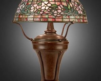 """A Tiffany Studios """"Dogwood"""" table lamp 27 A Tiffany Studios """"Dogwood"""" Table Lamp Late 1904/early 1905; New York, NY Shade signed: Tiffany Studios / New York / 1553-6; Base signed: Tiffany Studios / New York / 7876 The pink and green leaded glass """"Dogwood"""" banded shade on a three-light patinated bronze urn-form converted oil lamp base, electrified Overall: 21"""" H x 14"""" Dia. Estimate: $8,000 - $12,000"""