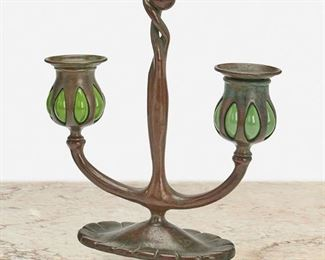 """35 A Tiffany Studios Double-Arm """"Bud"""" Candlestick Circa 1902-1919; New York, NY Signed: Tiffany Studios / New York / 1230 / [T.S. monogram] The patinated bronze """"Bud"""" candlestick with fluted oval base issuing two arms terminating in green blown glass capitals with removable bobeches 9"""" H x 7.75"""" W x 3"""" D Estimate: $400 - $600"""