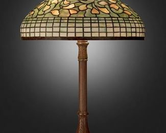 """37 A Tiffany Studios """"Vine Ornament"""" Table Lamp Circa 1902-1919; New York, NY Shade signed: Tiffany Studios / New York; Base signed: Tiffany Studios / New York / 638 The green and yellow leaded glass """"Vine Ornament"""" shade with geometric skirt on a three-light patinated bronze """"Library"""" base with fluted stem, round foot, and floral and leaf motifs, electrified Overall: 31"""" H x 20"""" Dia. Estimate: $8,000 - $12,000"""