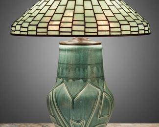 """39 A Tiffany Studios Leaded Glass And Rookwood Pottery Table Lamp First-quarter 20th Century Shade signed: Tiffany Studios / New York / 1913; Base signed: [Rookwood monogram] / 191 A Z / AM [Albert Cyrus Munson] The aquamarine-colored Tiffany Studios leaded glass cone shade with stepped brick pattern on a three-light, matte sea green drip glaze Rookwood pottery base with a baluster-form body and incised geometric designs raised on three scrolled foliate feet, electrified Overall: 23"""" H x 18"""" Dia. Estimate: $7,000 - $9,000"""
