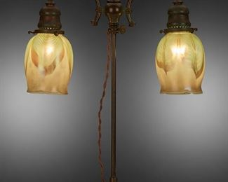 """41 A Tiffany Studios Double-Arm Table Lamp Circa 1902-1919; New York, NY Shades signed: L.C.T.; Base signed: Tiffany Studios / New York / 304 The two green and gold iridescent Favrile glass floriform shades with pulled feather motif on a patinated bronze double-arm, adjustable armature base with verdigris patination and engraved foliate and teardrop motifs, electrified Overall: 20"""" H x 13.5"""" Dia. Estimate: $4,000 - $6,000"""
