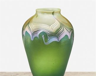 """47 A L.C. Tiffany Favrile Glass Vase 1902; New York, NY Signed: L.C.T. / Q 4494 The urn-form Favrile glass vase with green iridescent body, cream iridescent neck, and pulled feather transition 6.5"""" H x 4.5"""" Dia. Estimate: $600 - $800"""