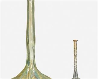 """48 Two L.C. Tiffany Favrile Glass Bud Vases Circa 1892-1893; New York, NY Each appears unsigned; First marked: X 2120; Second marked: X 1823 Each with experimental translucent iridescence over clear glass, comprising one large vase with bulbous base and slender stem and one small vase with bulbous base and spiral stem, 2 pieces Larger: 9.75"""" H x 5"""" Dia.; Smaller: 6"""" H x 2.5"""" Dia. Estimate: $600 - $800"""