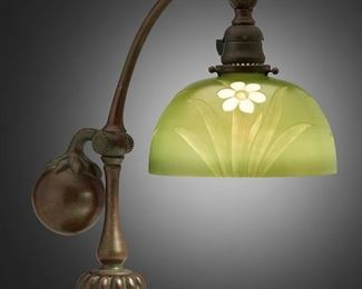 """50 A Tiffany Studios Counter-Balance Desk Lamp With Intaglio Shade Circa 1902-1918; New York, NY Signed: Tiffany Studios / New York / 415; Shade signed: L.C. Tiffany/ Favrile / Inc / 5136 M The intaglio Favrile glass shade with daffodils motif cut into green iridescent ground on a patinated bronze counter-balance base with stem-and-leaf design, weighted ball, and adjustable head, electrified Base: 16"""" H x 8"""" W x 14.5"""" D; Shade: 8"""" Dia. Estimate: $4,000 - $6,000"""