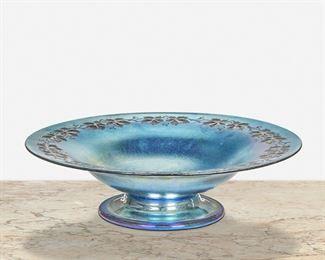 "59 A Blue L.C. Tiffany Favrile Glass Intaglio Compote First-quarter 20th Century; New York, NY Signed: L.C. Tiffany / Favrile The blue iridescent Favrile glass compote with an intaglio leaf and vine border 2.75"" H x 9.75"" Dia. Estimate: $500 - $700"