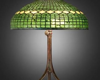 """64 A Tiffany Studios """"Vine Border"""" Table Lamp Circa 1902-1919; New York, NY Shade signed: Tiffany Studios / New York; Base spuriously signed: Tiffany Studios / New York / 393 The green and yellow leaded glass """"Vine Border"""" shade on a six-light patinated bronze Tiffany-style reproduction base in the form of three spreading root nodes, electrified Overall: 29"""" H x 20.5"""" Dia. Estimate: $4,000 - $6,000"""