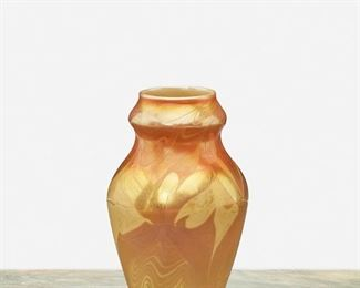 """66 A L.C. Tiffany Favrile Glass Cabinet Vase 1900; New York, NY Signed: L.C.T. / N 5350 The marbled gold iridescent Favrile glass vase with yellow swirls, wide-shouldered body, and flared neck 5.25"""" H x 3.25"""" Dia. Estimate: $700 - $900"""
