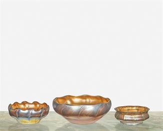 """68 Three L.C. Tiffany Favrile Glass Intaglio Bowls First-quarter 20th Century; New York, NY First signed: L.C.T. / Favrile; Second signed: L.C.T. / Favrile; Third signed: L.C. Tiffany / Favrile Each gold shaded to blue iridescent Favrile glass with intaglio cut leaf and stem motif to interior, comprising a large bowl with gently scalloped rim, a bowl with deeply scalloped rim and ribbed exterior, and a squat bowl with flared lip, 3 pieces Largest: 4"""" H x 10"""" Dia.; Smallest: 2.75"""" H x 6"""" Dia. Estimate: $700 - $900"""