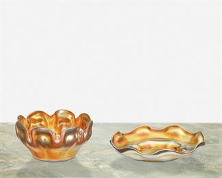 """72 A L.C. Tiffany Favrile Glass Finger Bowl And Ice Plate First-quarter 20th Century; New York, NY Bowl signed: L.C.T.; Ice plate signed: L.C.T. / Favrile Each gold iridescent with scalloped edge, comprising a bowl with ribbon-style edge and an ice plate, 2 pieces Bowl: 2.25"""" H x 4.5"""" Dia.; Ice plate: 1.25"""" H x 6"""" Dia. Estimate: $400 - $600"""